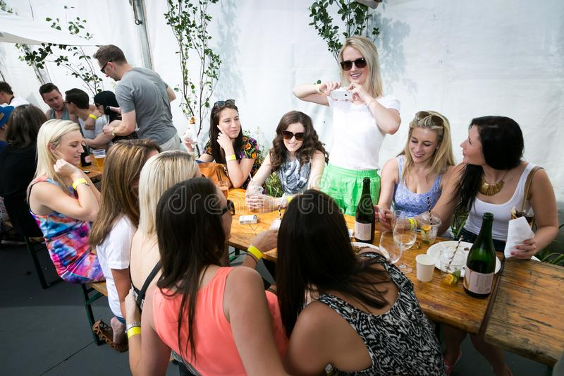 Diverse Friends eating, drinking and generally enjoying a day out at a Food and Wine Fair. Johannesburg, South Africa - November 8 2014: Diverse Friends eating royalty free stock photos
