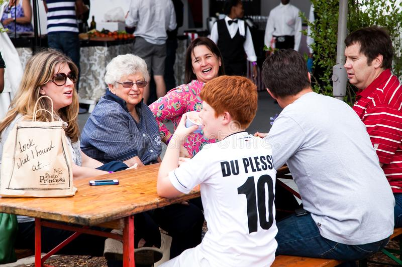 Diverse Friends eating, drinking and generally enjoying a day out at a Food and Wine Fair. Johannesburg, South Africa - November 24 2012: Diverse Friends eating royalty free stock images