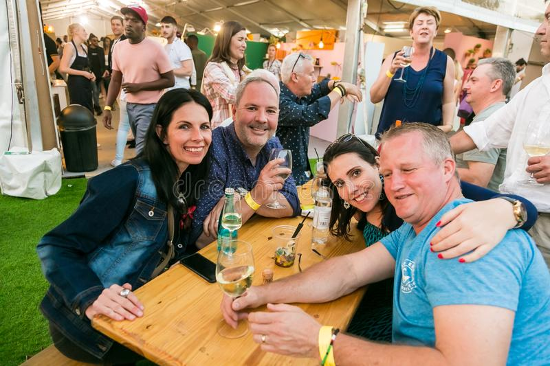 Diverse Friends eating, drinking and generally enjoying a day out at a Food and Wine Fair. Johannesburg, South Africa - October 14 2017: Diverse Friends eating royalty free stock photos