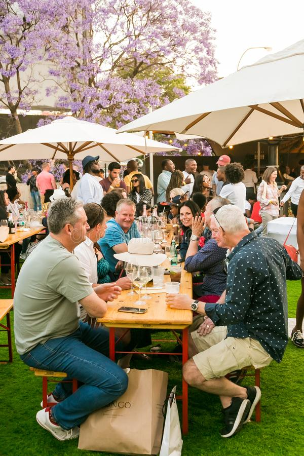Diverse Friends eating, drinking and generally enjoying a day out at a Food and Wine Fair. Johannesburg, South Africa - October 14 2017: Diverse Friends eating stock photos
