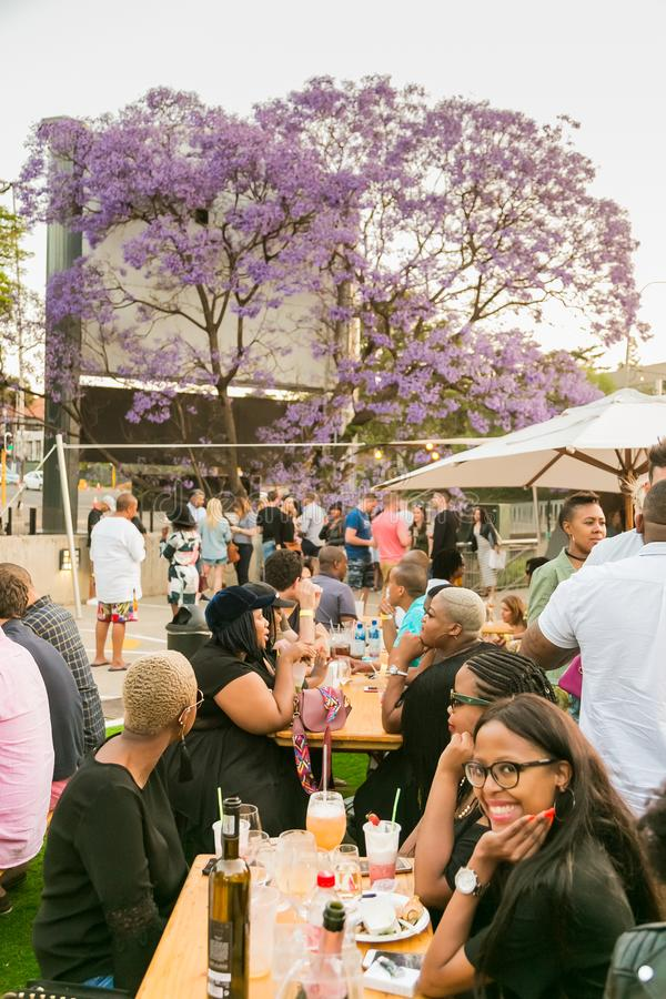 Diverse Friends eating, drinking and generally enjoying a day out at a Food and Wine Fair. Johannesburg, South Africa - October 14 2017: Diverse Friends eating royalty free stock images
