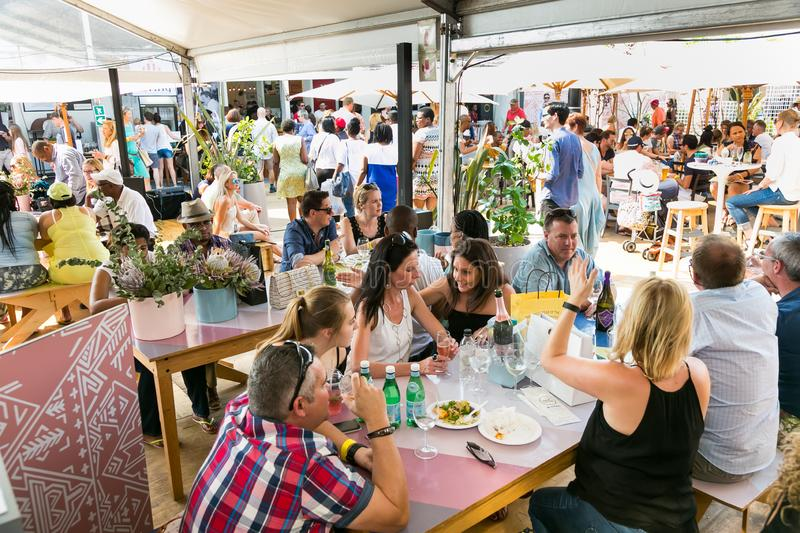 Diverse Friends eating, drinking and generally enjoying a day out at a Food and Wine Fair. Johannesburg, South Africa - October 10 2015: Diverse Friends eating stock photography