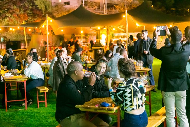 Diverse Friends eating, drinking and generally enjoying a day out at a Food and Wine Fair. Johannesburg, South Africa - October 12 2017: Diverse Friends eating stock photo