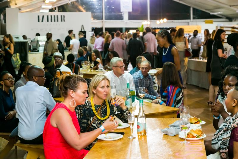Diverse Friends eating, drinking and generally enjoying a day out at a Food and Wine Fair. Johannesburg, South Africa - October 13 2016: Diverse Friends eating stock photography