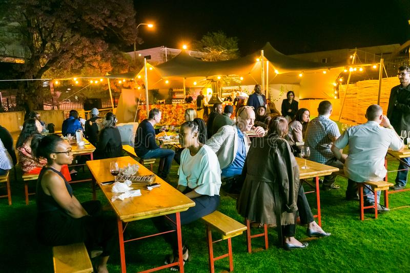 Diverse Friends eating, drinking and generally enjoying a day out at a Food and Wine Fair. Johannesburg, South Africa - October 12 2017: Diverse Friends eating stock image