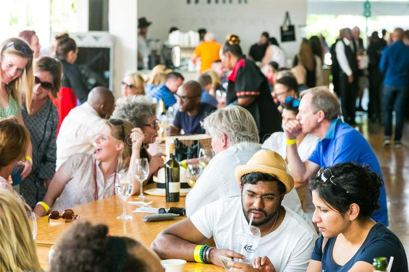 Diverse Friends eating, drinking and generally enjoying a day out at a Food and Wine Fair. Johannesburg, South Africa - October 15 2016: Diverse Friends eating stock photography