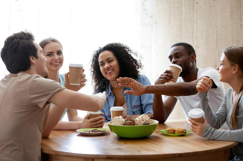 Cheerful diverse friends sitting together at table drinking coff royalty free stock photos