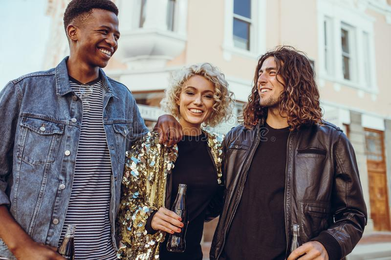 Diverse friends hanging out in the city. Group of three young friends walking down the city street. Young men and women hanging out in the city stock photography