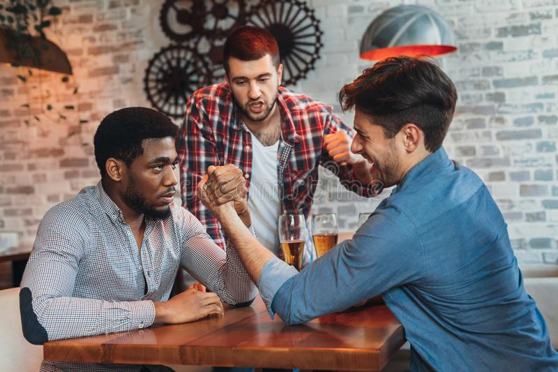 Diverse friends having fun and drinking beer in bar. Friends meeting. Diverse men having fun and drinking beer in bar stock photo
