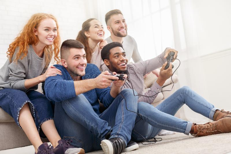 Diverse friends playing video games, having fun stock photos