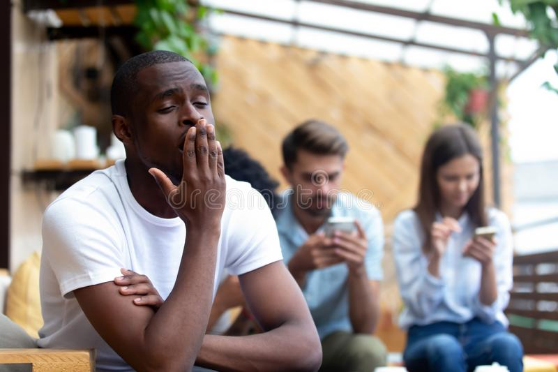 Diverse friends sitting in cafe focus on bored black guy royalty free stock photos