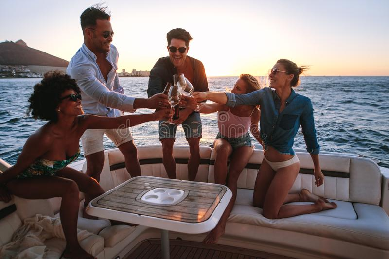 Diverse friends toasting drinks in boat party. Group of diverse men and women sitting at the back of the boat and toasting drinks. Young people partying on a royalty free stock images