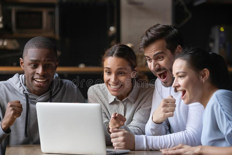 Diverse friends watching online game at laptop in public place. Multiracial friends sitting at table in cafe bar watching online game waiting lottery results use royalty free stock photos