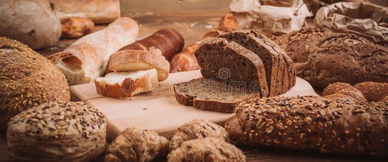 Diverse gebakken broden en broodjes op rustieke houten lijst royalty-vrije stock fotografie