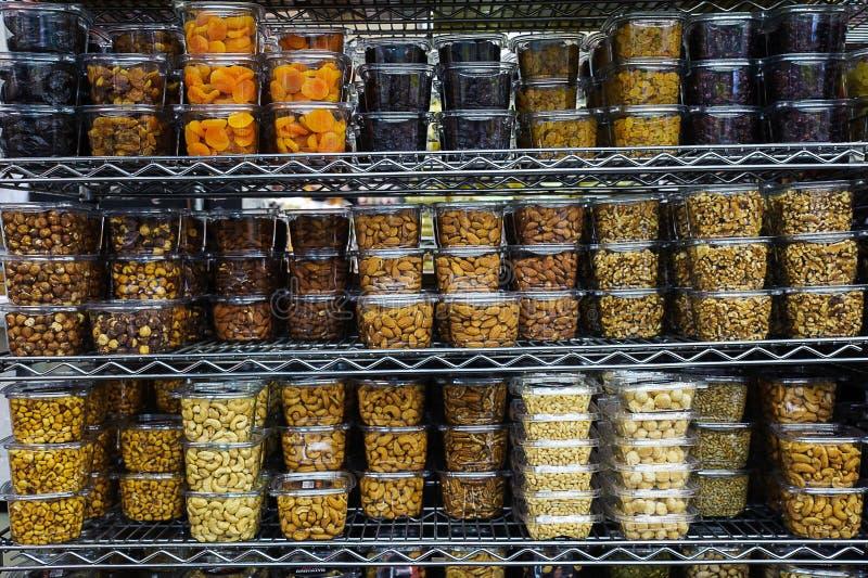 Diverse gedroogd fruit en noten in plastic containers die metaalplanken opvullen bij suppermarket royalty-vrije stock afbeeldingen