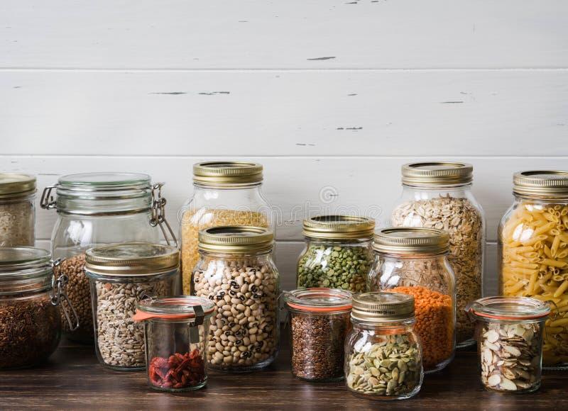 Diverse graangewassen en zaden - de erwten verdelen, zonnebloem en pompoen de zaden, bonen, rijst, deegwaren, havermeel, kouskous stock foto's