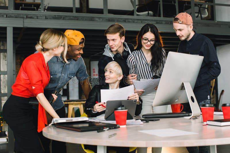 Diverse groep bedrijfsmensen die samen op modern kantoor samenkomen Vrouw in zwarte hoed die haar werk binnen tablet tonen aan royalty-vrije stock afbeeldingen
