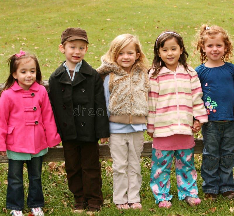 Diverse groep kleine jonge geitjes buiten stock foto's