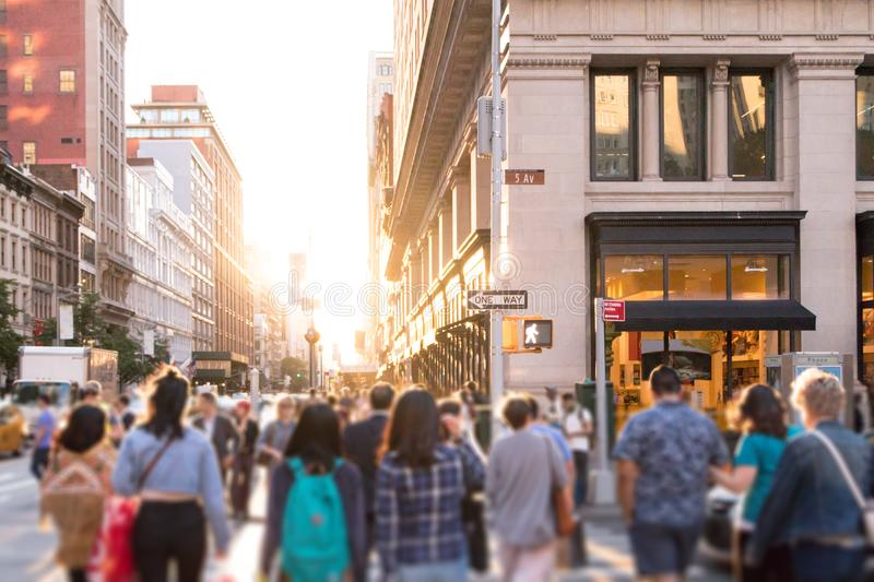 Diverse group of anonymous people walking down busy urban street in New York City stock photo