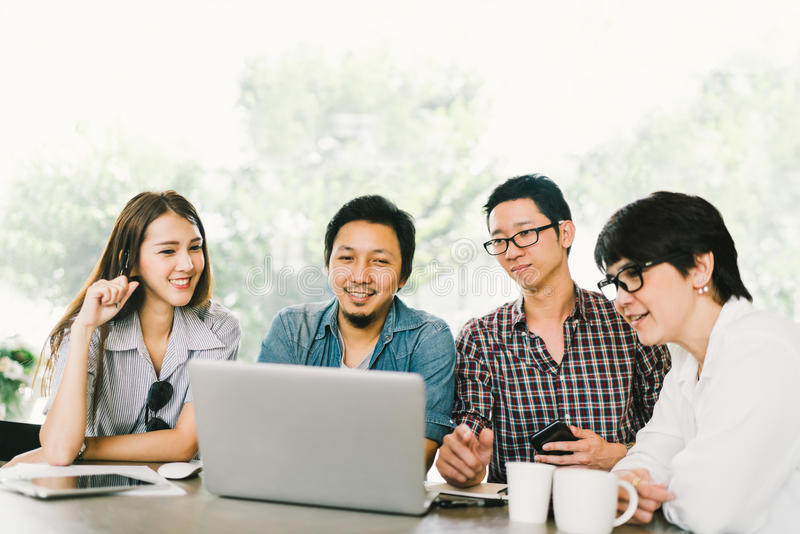 Diverse group of Asian business coworkers or college students using laptop in team casual meeting, startup project discussion. Or happy teamwork brainstorm royalty free stock photo
