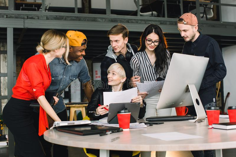 Diverse group of business people meeting together at modern office. Woman in black hat showing her work inside tablet to royalty free stock images