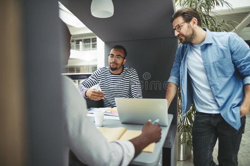 Diverse group of businessmen working together in an office pod royalty free stock photos