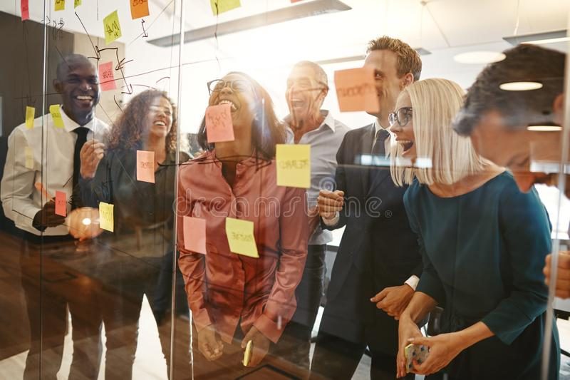 Diverse group of businesspeople laughing during an office brains royalty free stock image