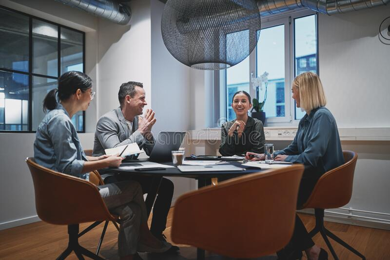 Diverse group of businesspeople laughing together during an offi royalty free stock photo
