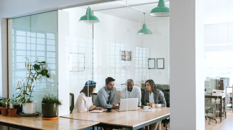 Diverse businesspeople using a laptop together in an office boardroom royalty free stock images