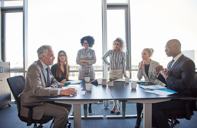 Diverse coworkers meeting together in a boardroom in an office royalty free stock images