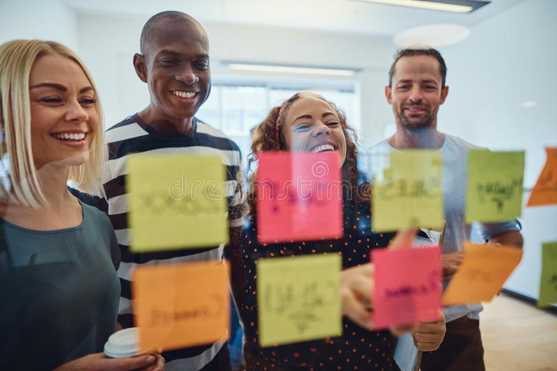Diverse group of designers laughing during an office brainstormi stock image