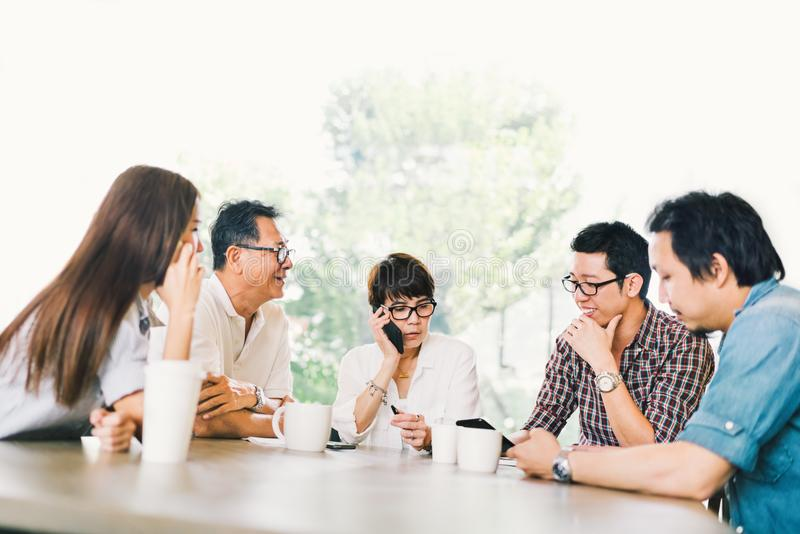 Diverse group of five Asian business person in team meeting at coffee shop or modern office. Strategic brainstorm, small business stock photo