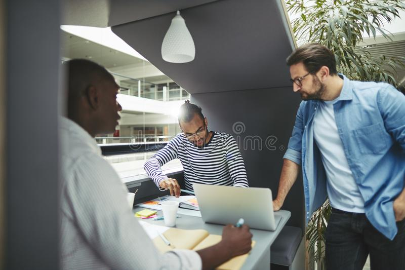 Diverse businessmen working in an office pod together stock photography