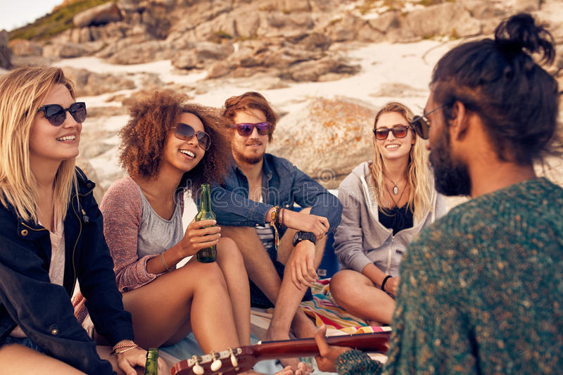 Diverse group of friends hanging out at beach stock images