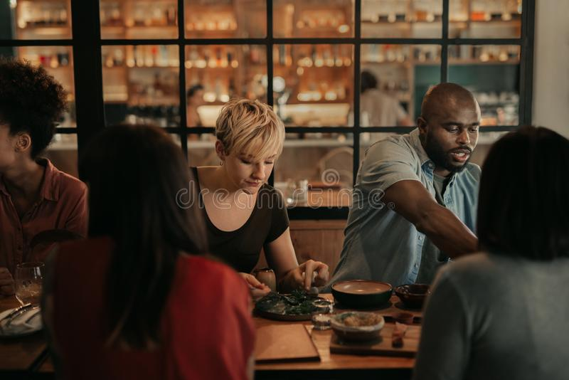 Diverse group of friends having a bistro meal at night stock photo