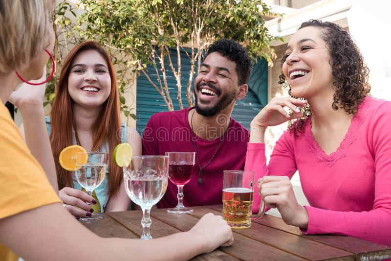 Diverse group of friends having fun at cafe bar outdoor. royalty free stock photography