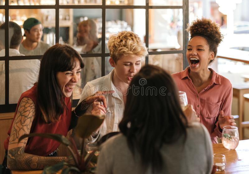 Diverse group of girlfriends laughing together in a trendy bar. Diverse group of young female friends sitting at a table in a trendy bar having drinks and stock image