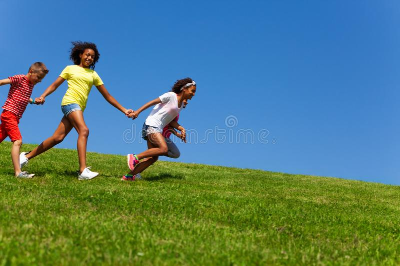 Diverse group of happy fast running children stock photography