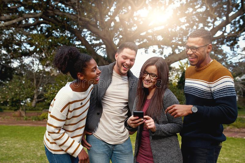 Diverse group of happy friends standing together laughing and looking at smart phone in the park - dressed very hip stock photography