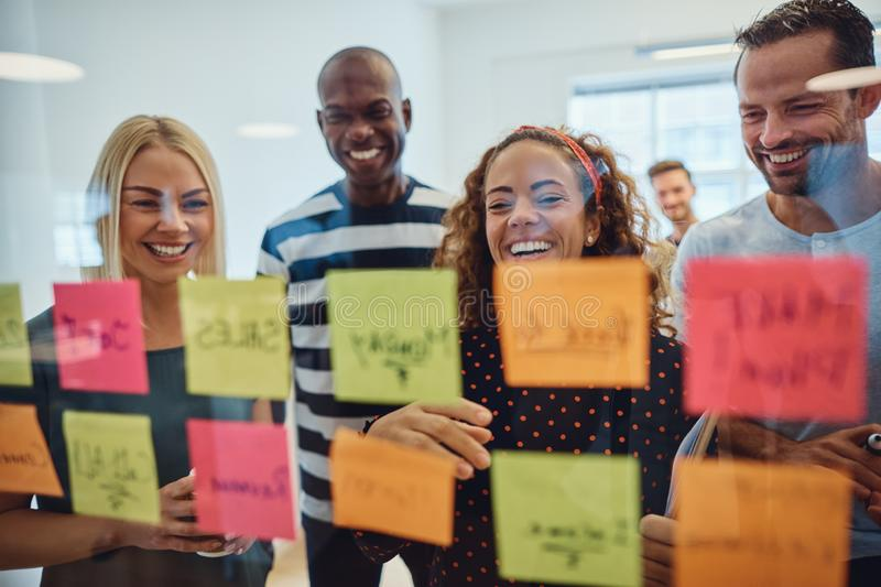 Laughing work colleagues brainstorming together in an office royalty free stock photography