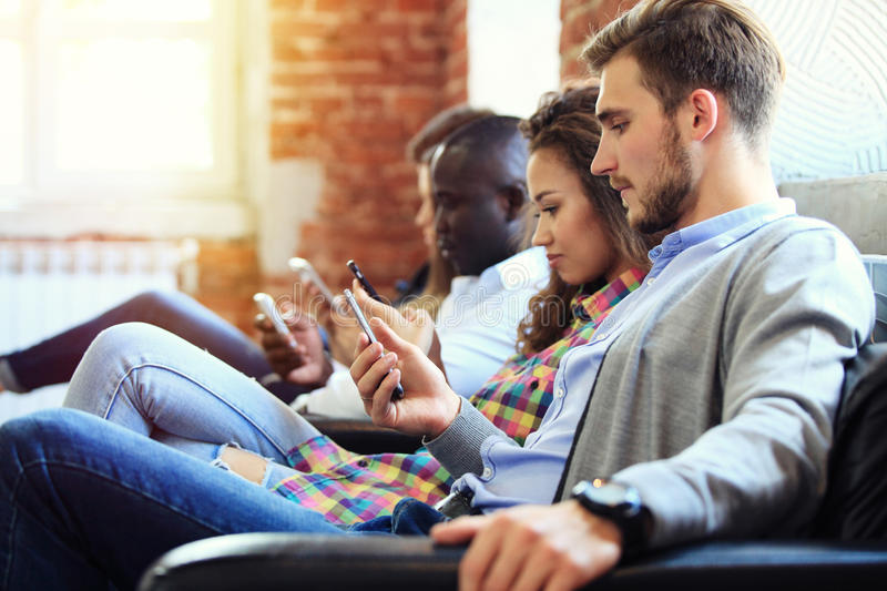 Diverse Group of People Community Togetherness Technology Sitting Concept. royalty free stock photo