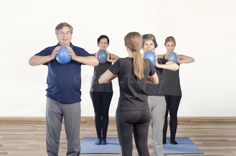 Diverse group of people a gym class doing ball Pilates exercise royalty free stock photo