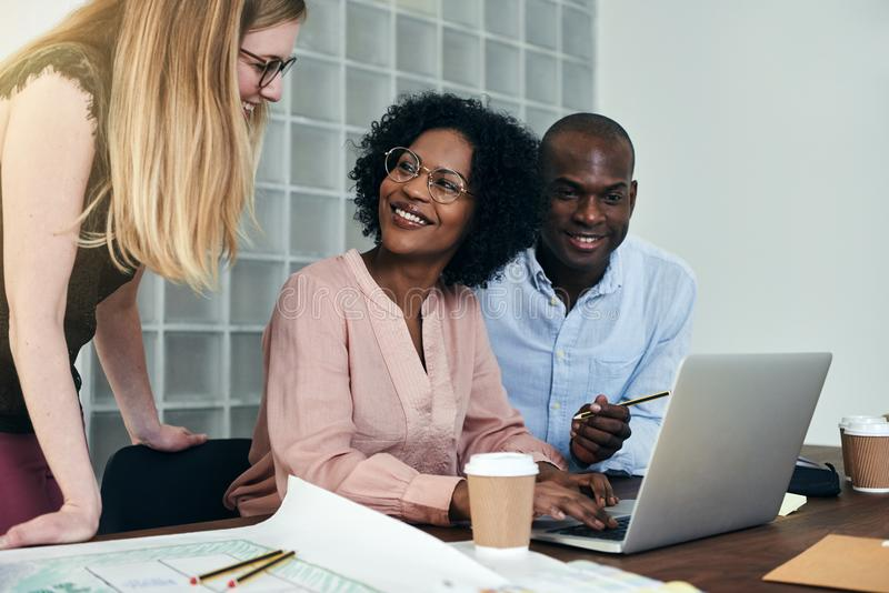 Diverse group of smiling colleagues working together in an office stock photos