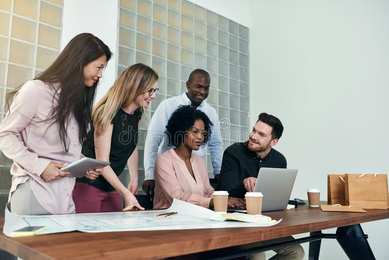 Group of smiling businesspeople working together around an office table stock photos