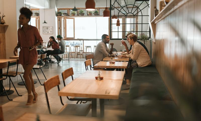 Friends talking together over drinks and lunch in a bistro stock images