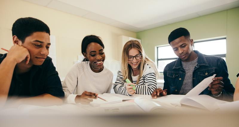 Diverse group of students preparing for exam. Diverse group of students with books preparing for exam in college classroom. Group of boys and girls studying with stock images