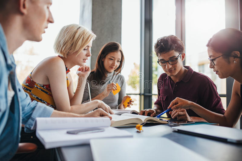 Diverse group of students studying at library stock photo