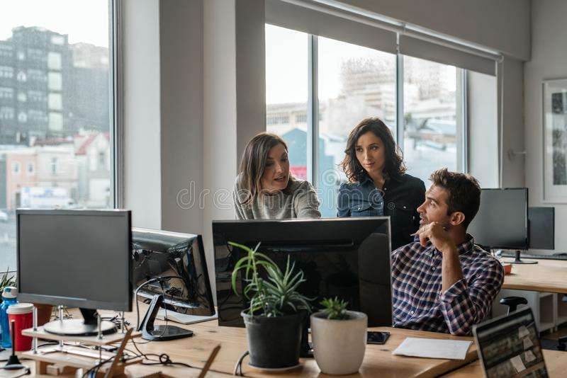 Diverse group of young designers working on a computer together stock images
