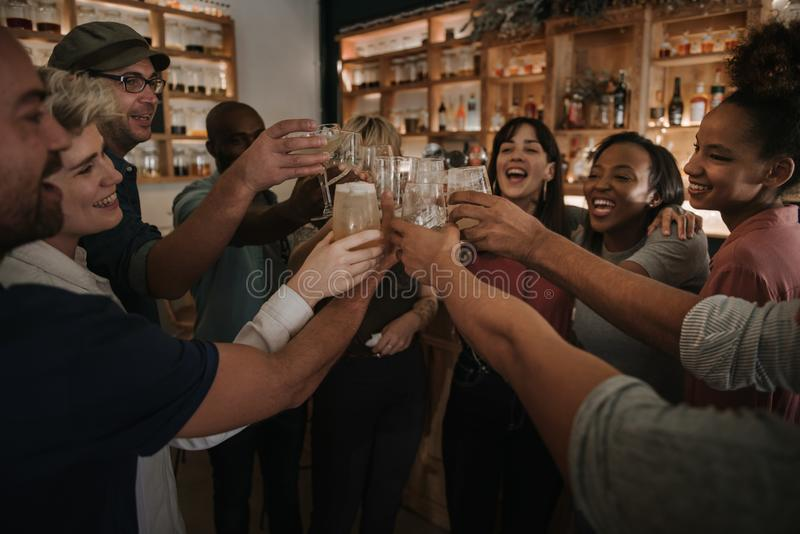 Friends cheering with drinks in a bar at night royalty free stock photography