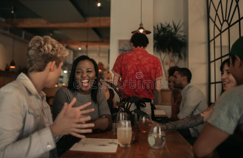 Laughing friends sitting at a bar table in the evening stock images